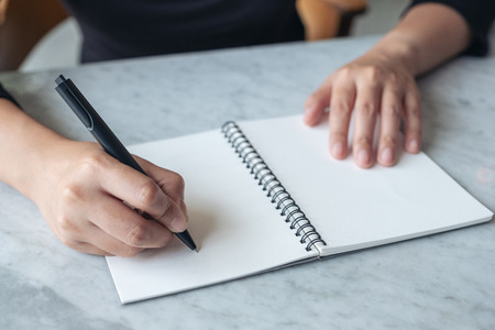 Closeup image of hands writing on blank notebook on the table Banco de Imagens - 109459494