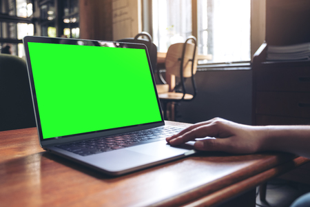 Mockup image of hand using and typing at laptop with blank desktop screen on wooden table in cafe Banco de Imagens - 109459501