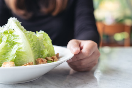 Closeup image of a woman holding and showing a plate of caesar salad on table in the restaurant Banco de Imagens - 109459502