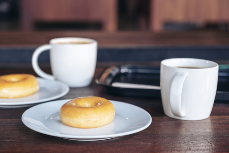 Two set of donuts in a white plate with coffee cups on wooden table Banco de Imagens - 109459360