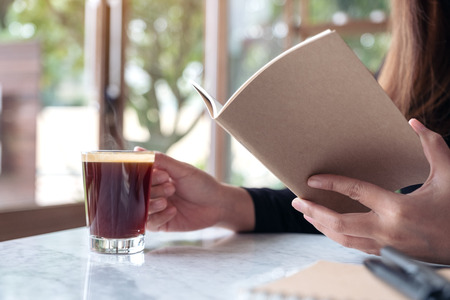 Closeup image of a business woman reading a book while drinking coffee in cafe