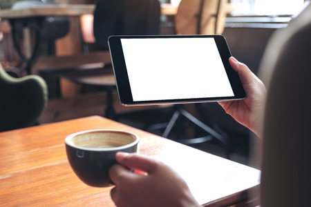 Mockup image of woman's hands holding black tablet pc with blank white screen while drinking coffee on wooden table in cafe