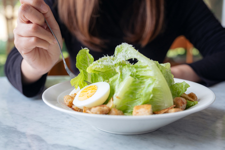 Closeup image of a woman eating caesar salad by fork on table in the restaurant Banco de Imagens