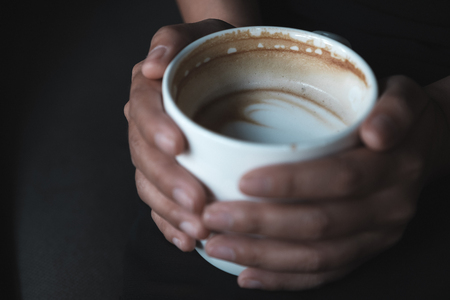 Closeup image of a woman's hands holding a white cup of hot coffee Banco de Imagens