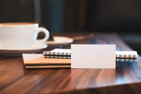 Closeup image of a white blank business card with notebooks and coffee cup on vintage wooden table