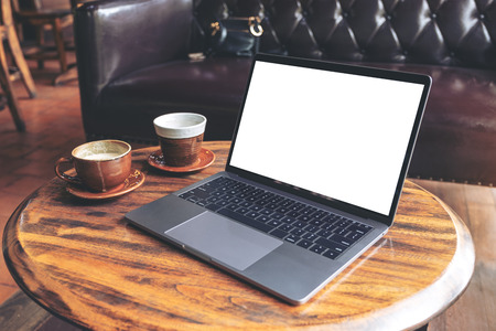 Mockup image of laptop with blank white desktop screen with coffee cups on wooden table in cafe