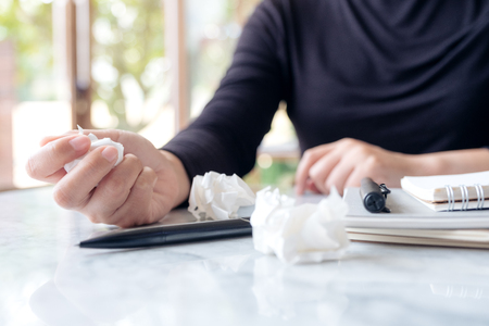 Closeup image of business woman working and squeezing papers on the table with feeling stressed and upset Banco de Imagens