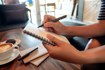 Closeup image of a woman's hands holding and writing down on a white blank notebook in cafe Banco de Imagens - 109459377