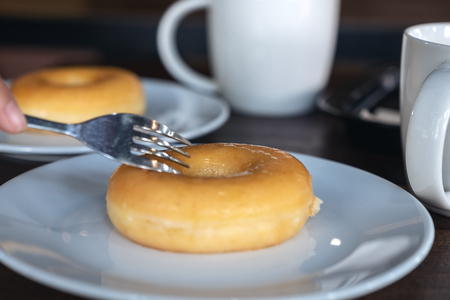 A hand cutting a piece of donut by fork in a white plate with coffee cups on table Banco de Imagens - 109459379