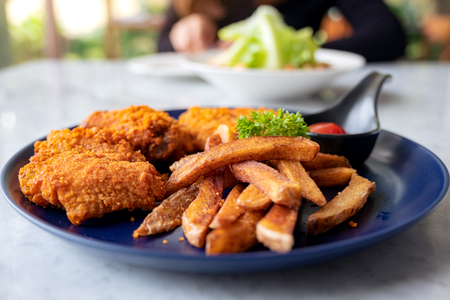 Closeup image of a plate of fried chicken and french fries with a woman eating salad in the restaurant Banco de Imagens - 109459382