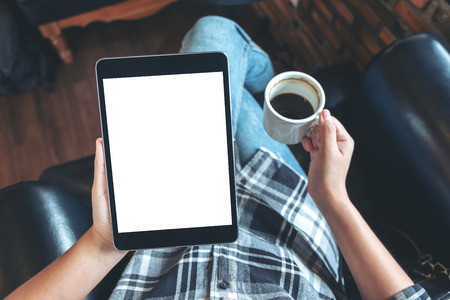 Top view mockup image of a woman sitting cross legged and holding black tablet pc with blank white desktop screen while drinking coffee in cafe Banco de Imagens - 109459383