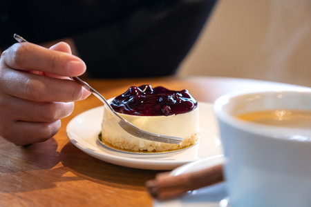 A woman's hand holding a fork to cut a piece of blueberry cheese cake to eat with coffee cup on wooden table Banco de Imagens