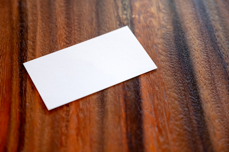 A white blank business card on vintage wooden background
