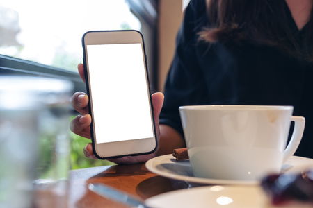 Mockup image of a woman holding and showing white mobile phone with blank screen with coffee and cake on the table in cafe Banco de Imagens