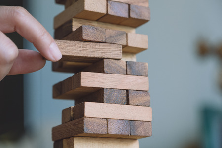 Closeup image of a hand holding and playing Tumble tower wooden block game