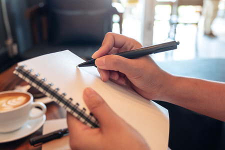 Closeup image of a woman's hands holding and writing down on a white blank notebook in cafe