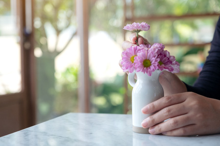 A woman arranging beautiful pink flowers in a white small vase on the table