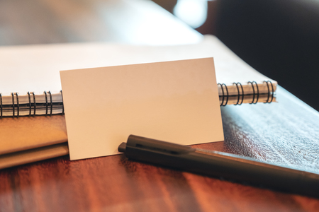 Closeup image of a white blank business card with notebooks and pen on vintage wooden table