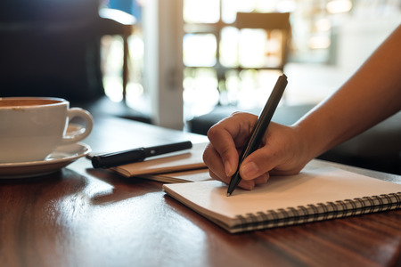 Closeup image of a hand writing down on a white blank notebook with coffee cup on wooden table Banco de Imagens - 109459385