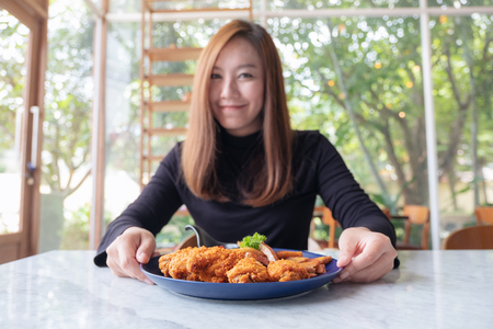 Closeup image of a beautiful asian woman holding and showing a plate of fried chicken and french fries in restaurant