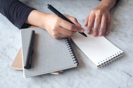 Closeup image of hands writing on blank notebook on the table