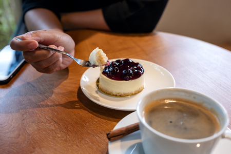 A woman's hand holding a fork to cut a piece of blueberry cheese cake to eat with coffee cup on wooden table Banco de Imagens - 109459133