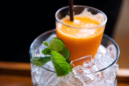 A glass of mixed orange and carrot juice in a jar of ice with mint leaves Banco de Imagens - 109459136