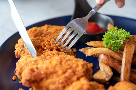 Closeup image of a person using knife and fork to eat fried chicken and french fries in restaurant