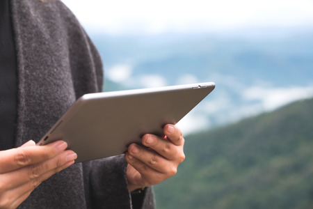 Closeup image of a woman holding and using tablet pc with green mountains on foggy day with blue sky background Banco de Imagens - 109459143