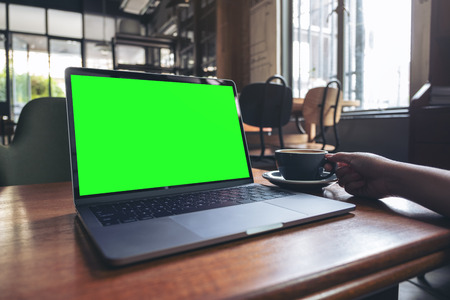 Mockup image of a woman using laptop with blank desktop screen while drinking hot coffee on wooden table in cafe