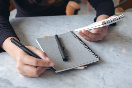 A woman holding and writing on notebook on the table