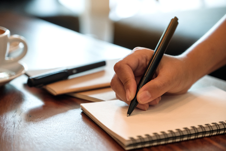 Closeup image of a hand writing down on a white blank notebook with coffee cup on wooden table Banco de Imagens