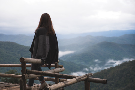 A woman sitting alone and looking at mountains on foggy day with blue sky background in the morning