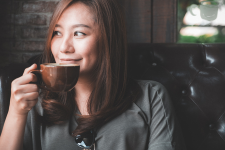 Closeup image of a beautiful Asian woman holding and drinking hot coffee with feeling good in vintage cafe