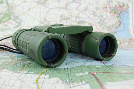 discreto: Binoculares sobre el mapa  Foto de archivo