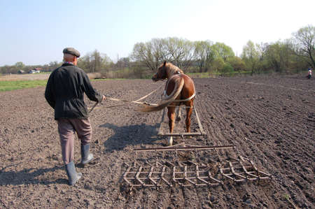 Farmer at work,plowing the land. photo