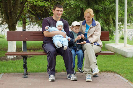sits: Family sits on  bench in a park