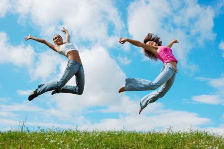 草原の女の子をジャンプ 写真素材