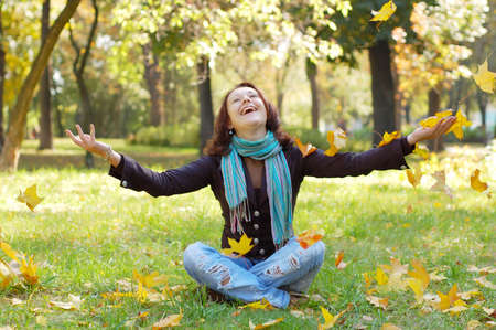 Young girl throwing autumn leaves Foto de archivo