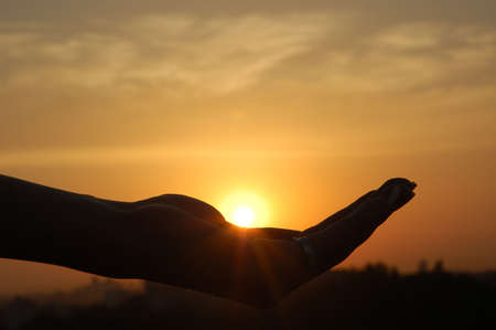 beautiful sunshine: Silhouette of hand on a background sunset Stock Photo
