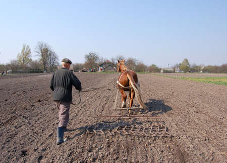 Farmer at work, plowing the land. photo