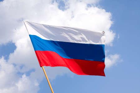 Russian flag on a background blue sky Foto de archivo