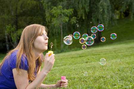 beautiful girl makes soap bubble on a grass photo