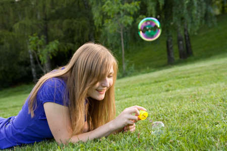 beautiful girl makes soap bubble on a grass Stock Photo - 3368619