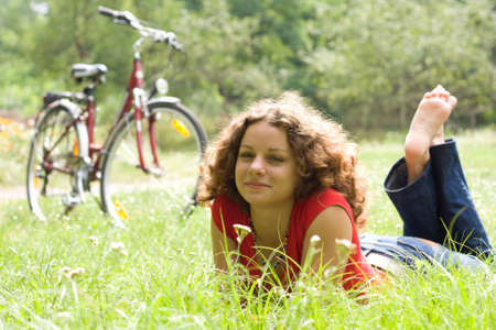 beautiful girl with a bicycle rests on a grass