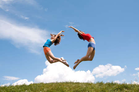 Jumping girls on meadow