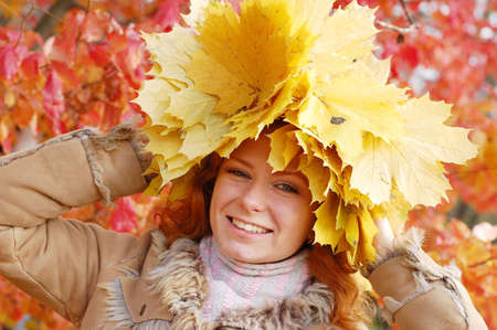 Portrait of beautiful girl in wreath of maple leaves photo