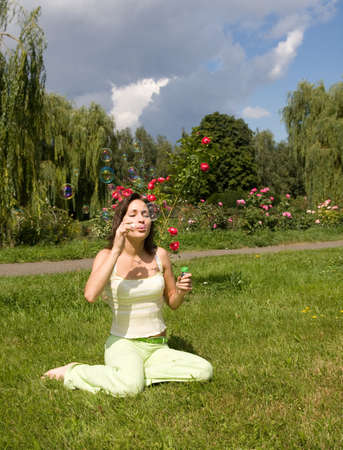 girl makes soap bubble on a grass photo
