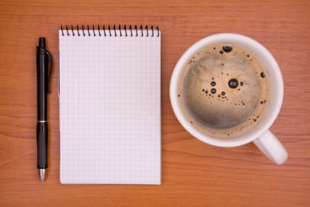 notebook and cup of coffee on desk