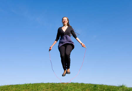 girl with skipping rope on a green meadow photo